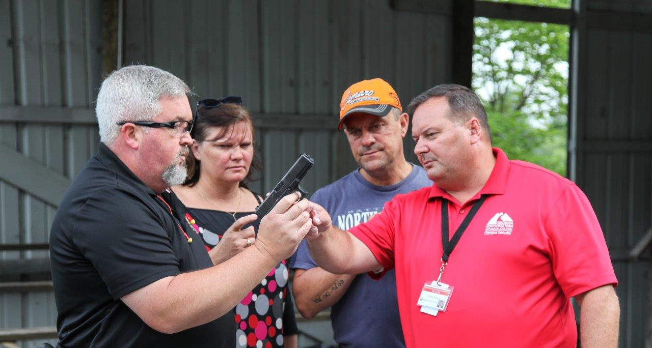 Georgia Northwestern Technical College Law Enforcement Academy Director Jim Pledger, left, displays some of the gun safety procedures his students learn during his program. From left are, Pledger, French Police Officer Lydie Stempfle, French Police Officer Alain Stempfle, and Georgia Northwestern Technical College staffer Fabrice Sainton.