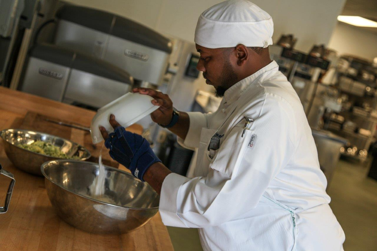 Georgia Northwestern Technical College Culinary Arts student Sedric Floyd of Rome, Georgia adds ingredients to a special muffin recipe he prepared during class at the Woodlee Building on the college's Floyd County Campus.