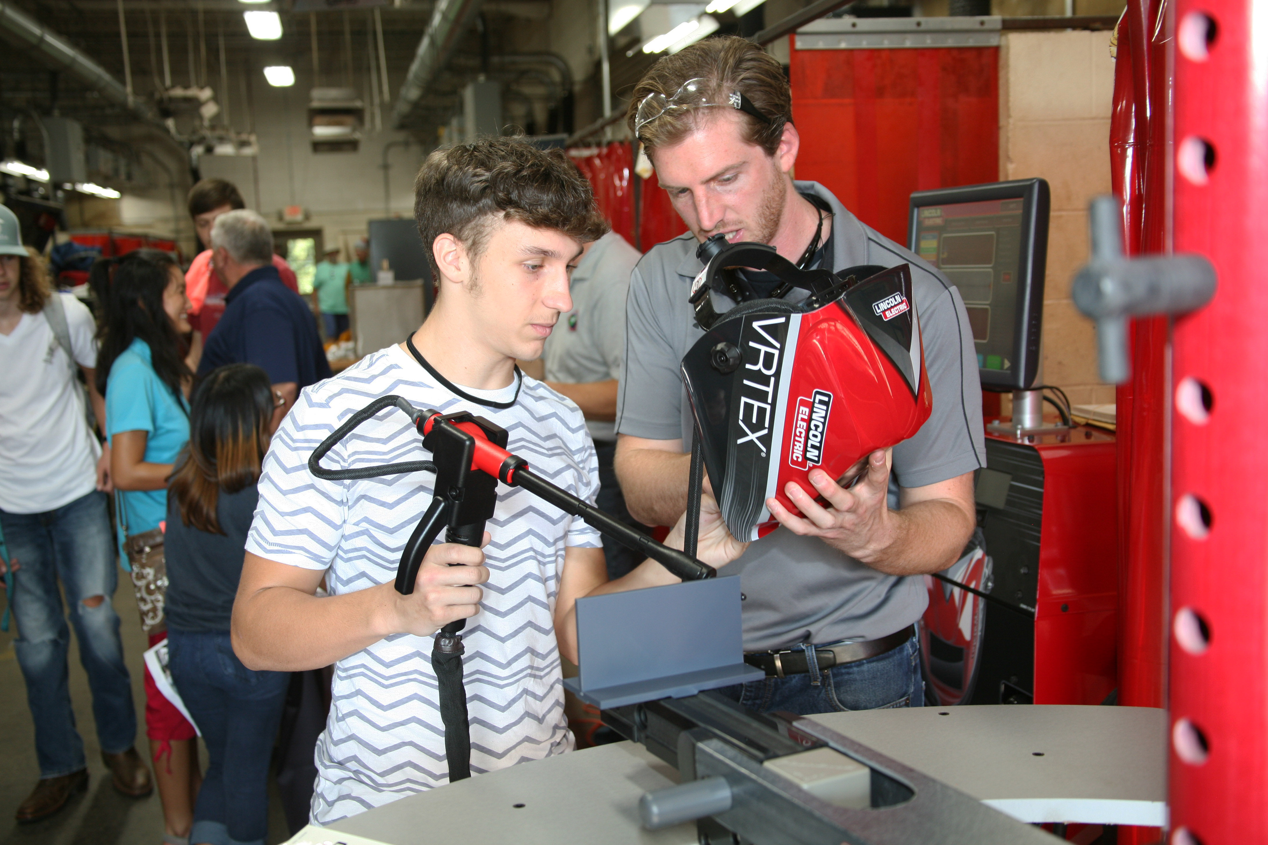Curt Metz (right) of Lincoln Electric, goes over the welding simulator with Kaleb Brondaway (left) of Rome High School.