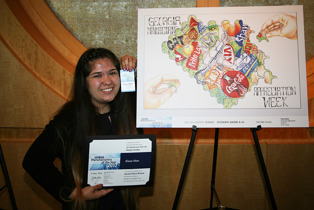Kiana Mata stands beside her artwork that won second place in the 2017 Manufacturing Appreciation Week (MAW) statewide student design contest in the ninth through twelfth grade category.