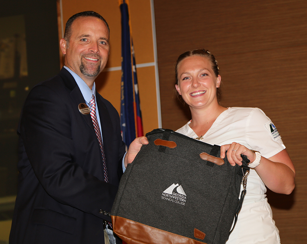 Kimberlee Hall (right) of Gordon County was presented with a tote bag by Stuart Phillips (left), interim president of GNTC, during GNTC's Student Recognition Reception. Hall won the gold medal in Practical Nursing at SkillsUSA Georgia and will compete in the national SkillsUSA competition.