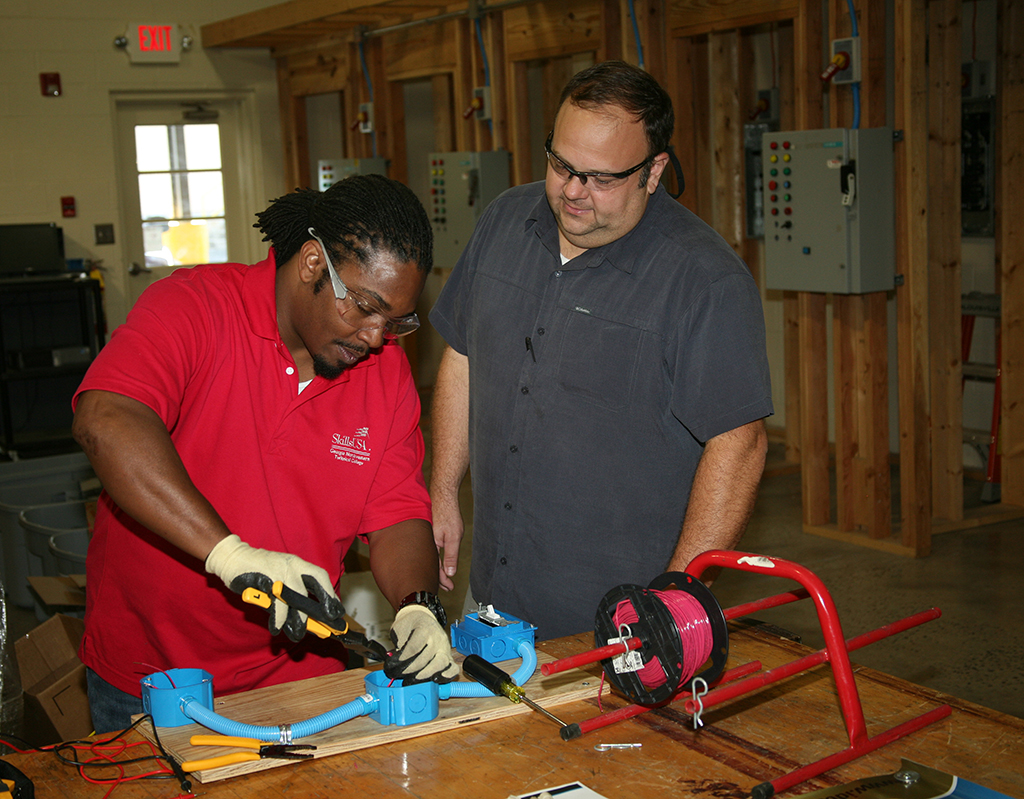 Melvin Mitchell (left), of Cartersville, works with IDEAL tools while Scott Carter (right), director of Electrical Systems Technology at GNTC, supervises in the electrical lab on the Floyd County Campus. Mitchell was part of the Career Pathways team that won the gold medal in the SkillsUSA Georgia competition and the bronze medal in the national SkillsUSA competition.