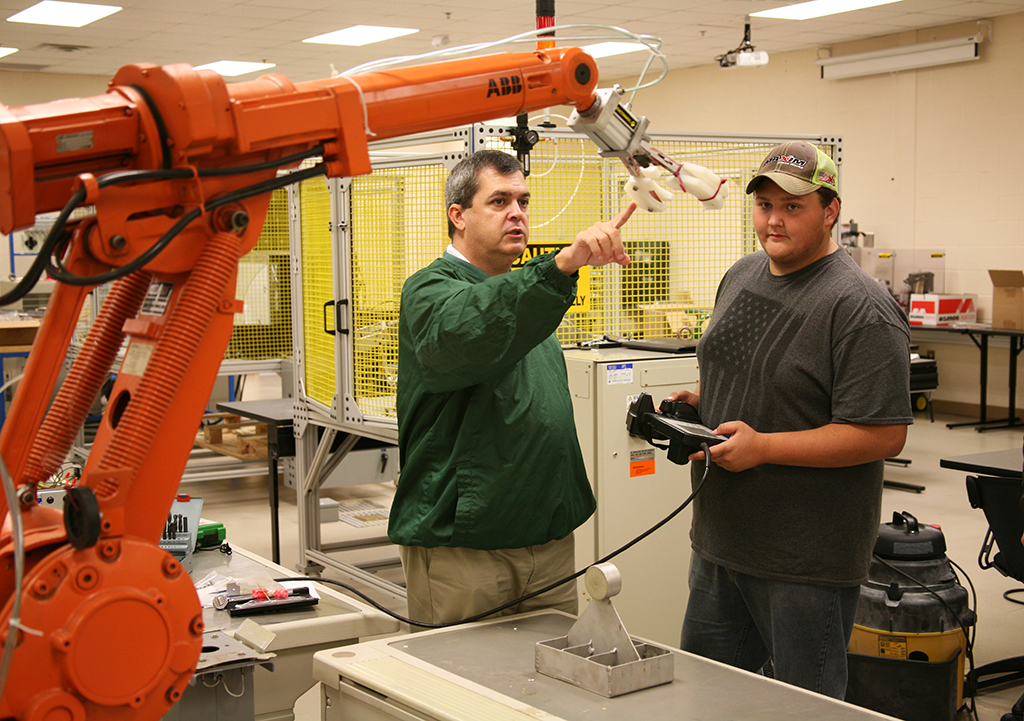 Greg Smith (left), instructor of Robotics and Engineering at the Floyd County Schools College and Career Academy (FCSCCA), teaches Camron Roubieu (right), of Coosa High School, how to operate an industry-grade robot. Robotics and Engineering is a Move On When Ready program between FCSCCA and Georgia Northwestern that gives students the opportunity to earn college credits while still in high school. Students may also use the credits earned towards an industry certificate or associate degree.
