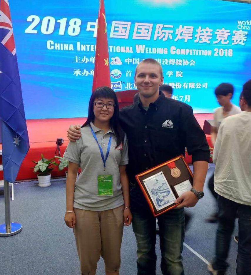 Ryan Fincher (right) of Cedartown poses for a picture with his interpreter after winning the bronze medal in in the China International Welding Competition 2018 in Beijing.