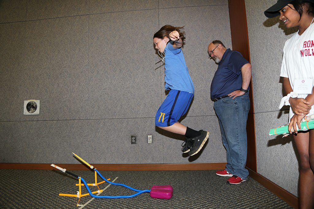 Theo Scott (left), rising eight-grader at Rome Middle School, jumps in the air to launch the rockets he built in Aerospace Engineering during the Young Scholars Program at GNTC. Also pictured is Jaya Cooper (right), rising eighth-grader at Rome Middle School, and Randy Stafford (center), Physics Teacher at Rome High School.