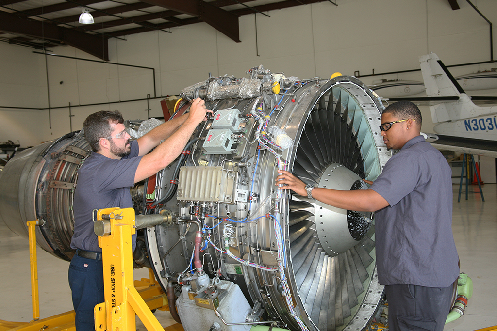 Drew Ware (left) of Cave Spring and Lawrence Peters (right) of Austell work on the CFM56-3B1 high-bypass turbofan engine that was donated to GNTC by Southwest Airlines.