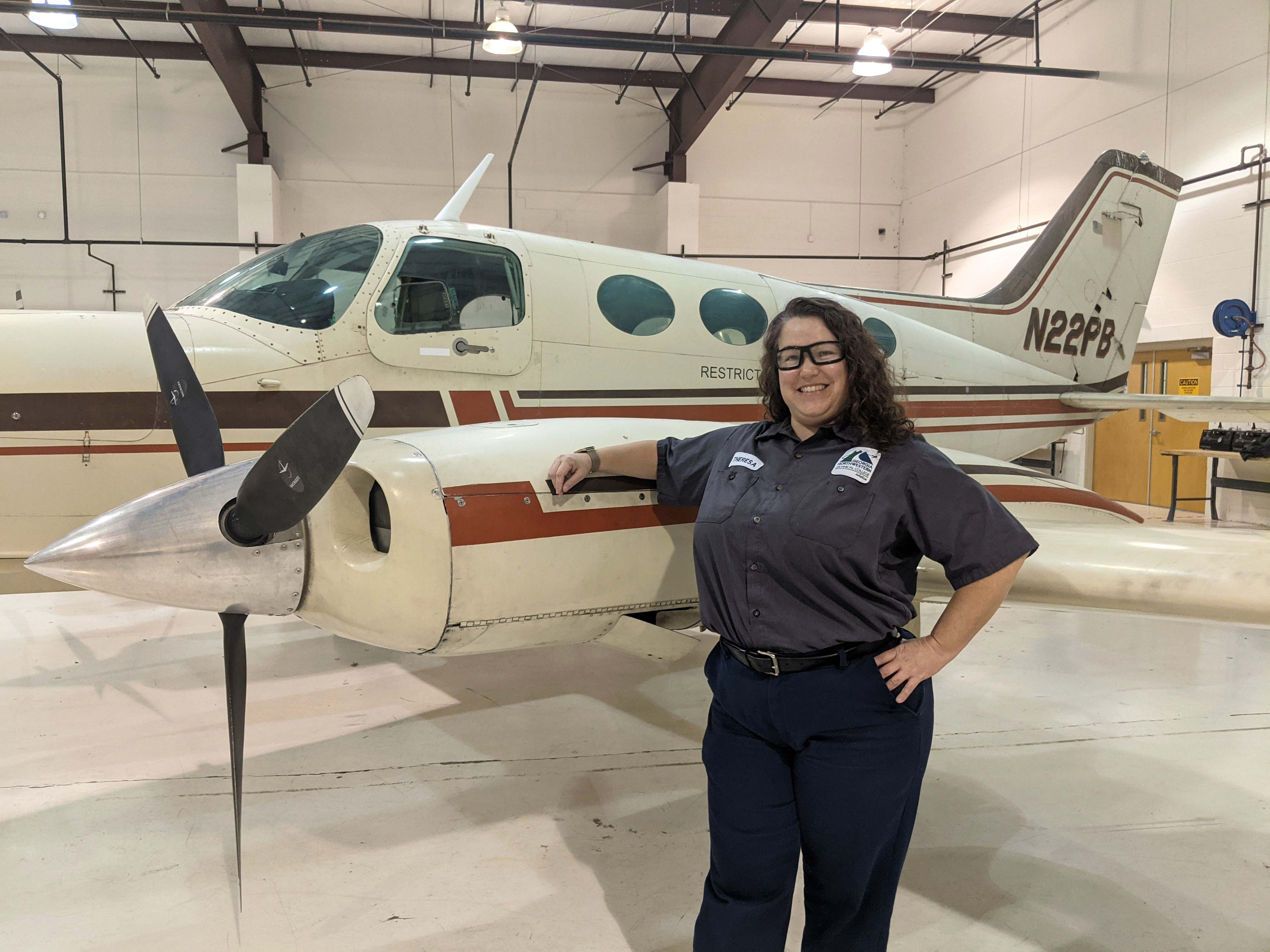 GNTC student Theresa Harper stands next to a plane in the GNTC Aviation Training Center hangar. Harper is the recipient of the HAI/WAI Maintenance Technician Certificate Scholarship and will receive recognition at the 32nd Annual International Women in Aviation Conference in March.